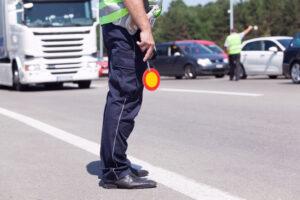 Politimand med stopskilt fartskriver
